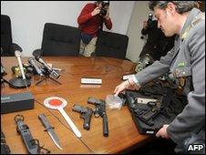 A member of Italy's finance police shows guns, bullets and other weapons seized in Milan, 3 March 2010