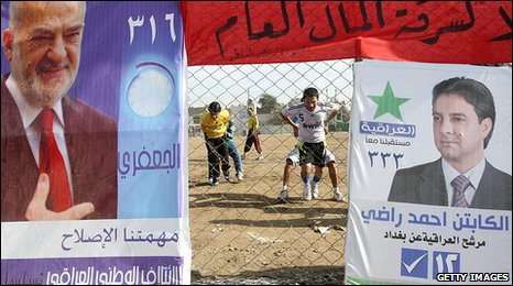 Iraqi youths play football in a field adorned with campaign posters