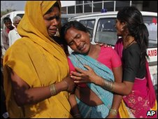 An unidentified woman is comforted after a stampede at a temple in Kunda, 180 kilometers (112 miles) southeast of Lucknow, Uttar Pradesh - March 4, 2010