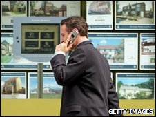 Man walks past estate agent's window