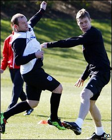 Shawcross (right) challenges Wayne Rooney during England training