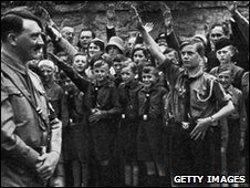Nazi leader Adolf Hitler smiles while uniformed Hitler Youth salute him outdoors in Erfurt, Germany