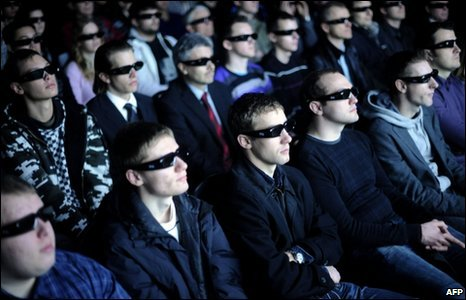 Visitors wearing 3D glasses watch a videoclip at the stand of US visual computer technologies company Nvidia