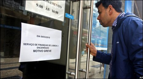 Man reads a note on the door of a tax office in Lisbon (4 March 2010)