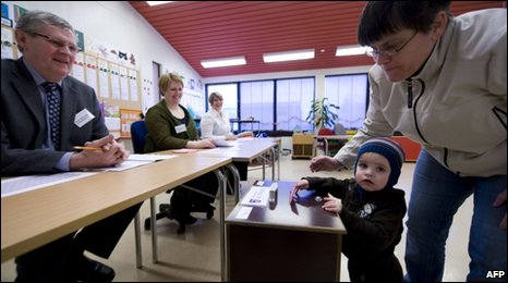 Election employees smile as a mother votes with her infant son in Alftanes, Iceland, 6 March