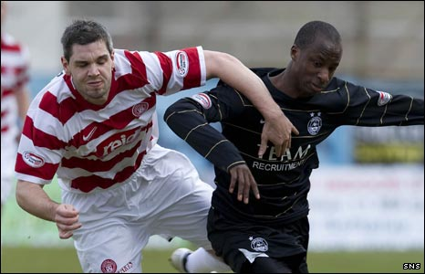 Hamilton's David Elebert (left) tussles with Sone Aluko 