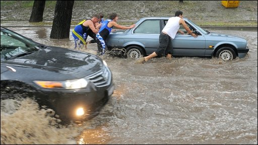 People help to push a car down a street in Melbourne after the sudden hail storm
