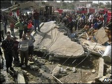 Residents gather at the scene of a blast which destroyed a building in northern Baghdad, 7 March 2010