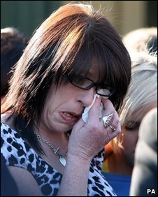 A woman wipes away a tear at the memorial service for the two soldiers