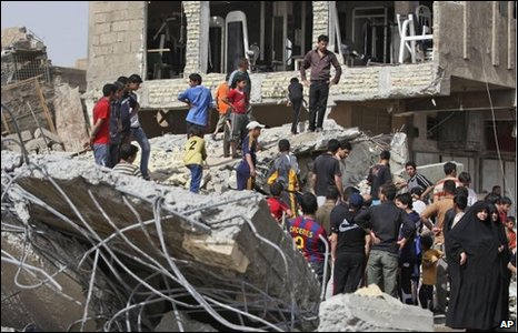 Iraqis at the scene of a collapsed block of flats after a bomb attack in Baghdad