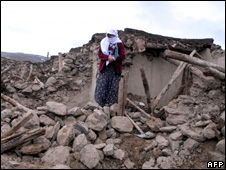 Elderly woman stands next to her collapsed home (8 March 2010)