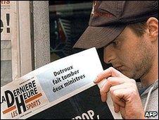 A Belgian man reads La Derniere Heure