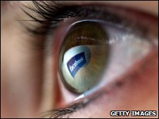 A human eye with the 'Facebook' logo reflected into it