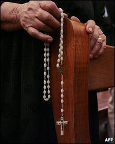 Woman with rosary in church