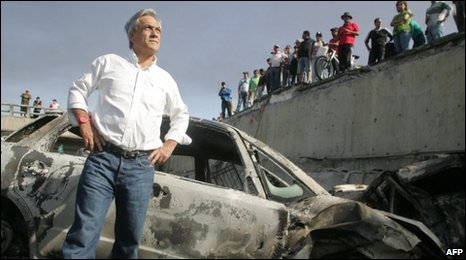 Sebastian Pinera stands by destroyed cars in Concepcion on 28 February
