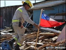 A fireman places a Chilean flag amid the rubble of buildings  in Dichato
