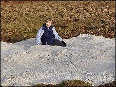 Image shows Swansea Met artist Ann Jordan with the blanket sitting  on top of the Black Mountain