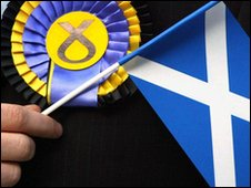 A man wearing an SNP rosette and holding a St Andrews flag