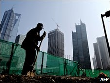 File image of worker using shovel at Shanghai building site