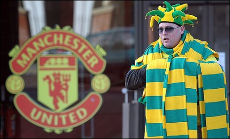 A street pedlar sells green and gold scarves outside Old Trafford