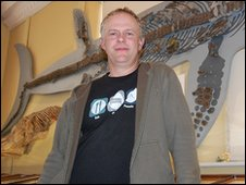 Geologist, Paddy Howe, standing infront of 'Kevin' the ichthyosaur skeleton