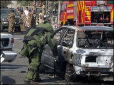 A bomb disposal expert checks a wrecked car after one of the earlier blasts in Lahore, 12 March