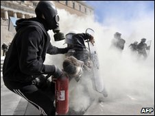 A demonstrator pulls another protester away from riot police during clashes outside the Greek parliament in Athens on 5 March 2010