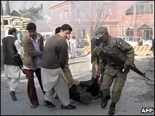 Pakistani soldier and local residents carry an injured policeman in Saidu Sharif. Photo: 13 March 2010