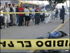 A police line where the body of a man lies in Acapulco, Mexico, on 13 March 2010
