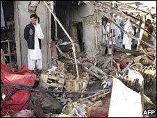 Afghans inspect the site of one of the blasts in Kandahar. Photo: 14 March 2010