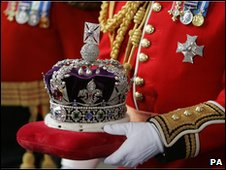 Britain's Queen Elizabeth II's crown is carried out of The House of Lords after the State Opening of Parliament