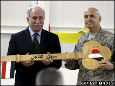 US Brigadier General David Quantock (R) hands Iraqi Minister of Justice Dara Nur al-Din a symbolic wooden key to Taji prison