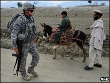 A US soldier walks past Afghan people (file image)