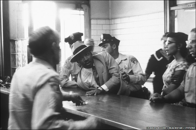 Martin Luther King, Jr being arrested as his wife look on