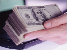Dollars by laptop.Corbis