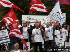 Workers with flags and banners protest at the closure