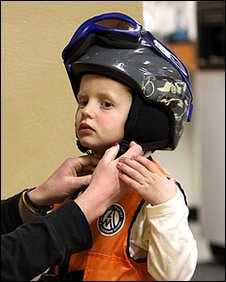 Child putting on ski helmet