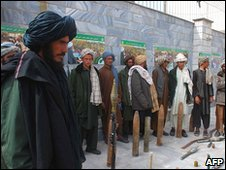 Surrendering Taliban militant fighters stand with their weapons as they are presented to the media at a government building in Herat on March 14, 2010