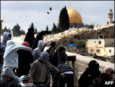 Backdropped by the golden Dome of the Rock mosque in Jerusalem's Al-Aqsa compound, Palestinian youths throw stones at Israeli soldiers
