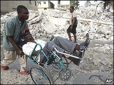 A man pushes a person in a wheelchair through earthquake rubble in Port-au-Prince, Monday, March 15, 2010