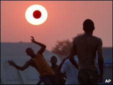 A ball is seen in front of setting sun at survivors' camp in Port-au-Prince on 13 March 2010
