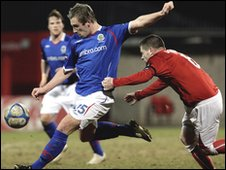 Cliftonville's Ciaran Donaghy fails to prevent Mark McAllister getting a shot away