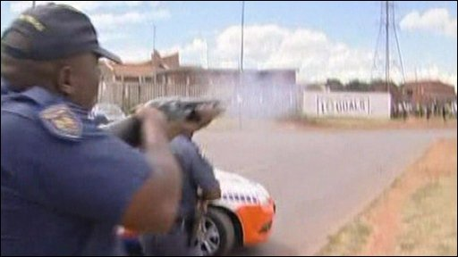 A police officer fires rubber bullets at youth protesters in South Africa
