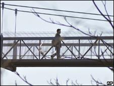 A Cornell University student walks across the Suspension Pedestrian bridge (16 March 2010)