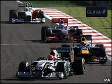 Mark Webber struggles to find a way past the Mercedes of Michael Schumacher in Bahrain