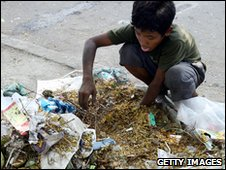 A Cambodian boy scavenges through rubbish