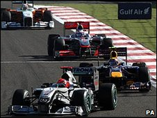 Michael Schumacher holds off Mark Webber's Red Bull and Jenson Button's McLaren in Bahrain