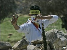 A Palestinian demonstrator uses a slingshot to hurl stones at Israeli soldiers near Nablus, 20 March 2010