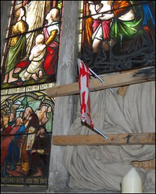 A broken stained glass window at St Peter's church in Copdock