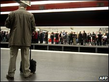 People wait at the suburban train station of Auber in Paris, 23 March 2010